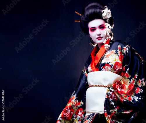 Fotografia young pretty geisha in kimono with sakura and decoration