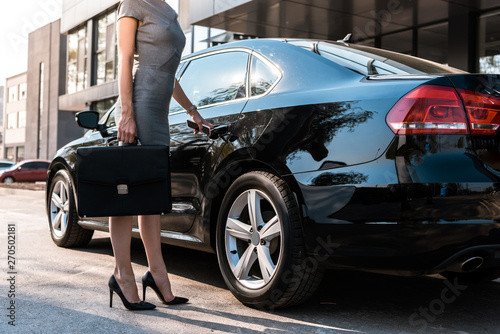 Poster Voitures rapides cropped view of businesswoman standing near black car with briefcase