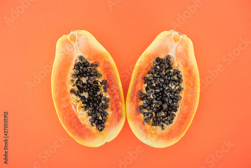 top view of ripe bright papaya halves with black seeds isolated on orange - 270505912