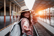 Smiling woman traveler looking camera with backpack on holiday relaxation at the train station,relaxation concept, travel concept