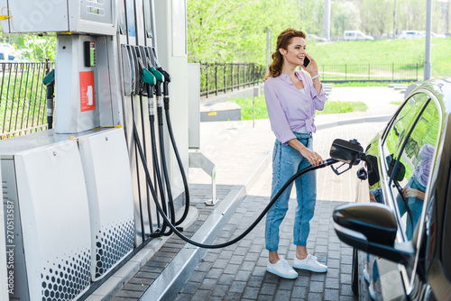Fotografie, Obraz  cheerful woman holding fuel pump while refueling car with benzine and talking on