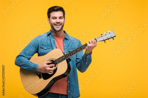 handsome smiling man playing acoustic guitar Isolated On yellow Tablou Canvas
