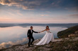 canvas print picture - Sensual wedding couple groom and bride in a long white dress standing on the edge of the mountains overlooking the lake holding hands together