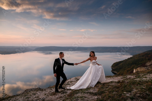 Sensual wedding couple groom and bride in a long white dress standing on the edg Fototapeta