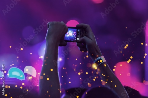 Audience with hands raised at a music festival and lights streaming down from above the stage. Soft focus, blurred movement. - 270523577