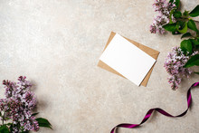 Flat Lay Of Kraft Envelope And Blank Paper Card With Copy Space Mock Up. Top View Home Office Desk Workspace Decorated With Lilac Flowers And Purple Ribbon. Beauty Blogger, Minimal Women Desk Concept.
