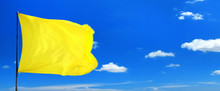 Conceptual Image Of Waving Blank Yellow Flag Over Sunny Blue Sky