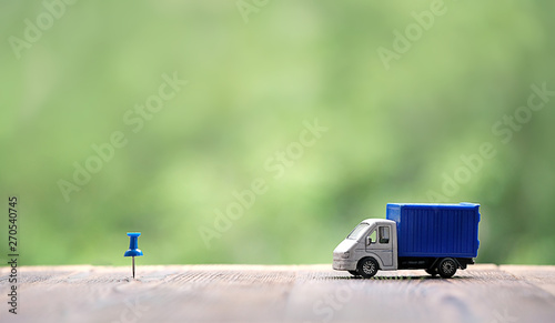 miniature van on wood background. truck toy and destination point indicated by blue pushpin. Concept for visualization of delivery services, logistics, business, forwarding, travel, cargo delivery. - 270540745