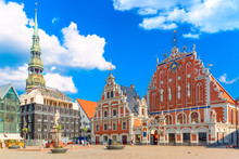 View Of The Old Town Ratslaukums Square, Roland Statue, The Blackheads House And St Peters Cathedral Against Blue Sky In Riga, Latvia. Summer Sunny Day