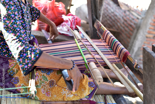 Fotografie, Obraz  Indonesian woman in a shop producing Songket Lombok in the village Sukarara whic
