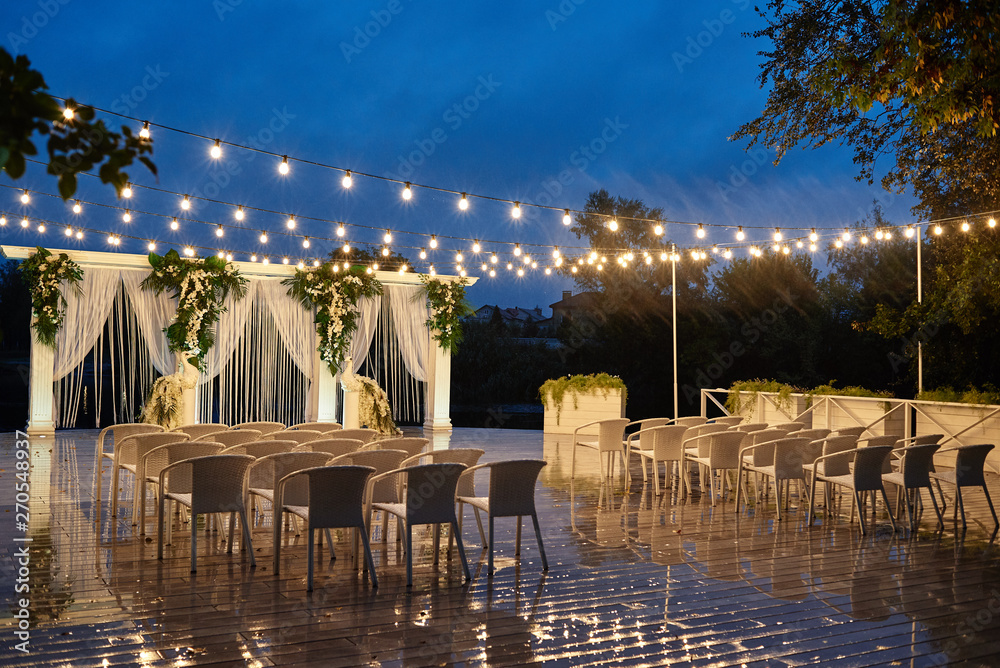 Fototapety, obrazy: Night wedding ceremony with arch, orchid flowers, chairs and bulb lights in forest outdoors, copy space. Wedding decorations