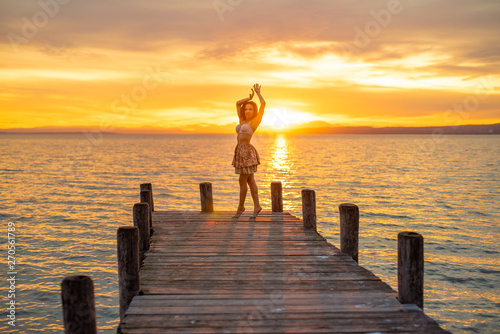 fototapeta na ścianę Happy woman enjoying the summery sunset at the lake on her vacation. The woman in bra and a short summer skirt laughs and puts her arms in the direction of the sky