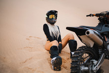 Woman With Long White Hair Sitting Near Cross Dirt Motorcycle In Desert