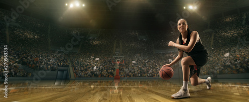 Photo Female basketball player with ball on big professional arena