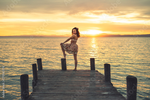 Tuinposter Pier Happy woman enjoying the summery sunset at the lake on her vacation. The woman in bra and short summer skirt laughs and poses at the end of the wooden walkway