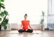 Leinwandbild Motiv Attractive young woman exercising and sitting in yoga lotus position while resting at home