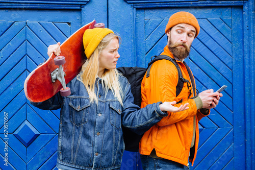 Photo Image of young hipster woman spying and peeking at smartphone of her boyfriend