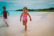Leinwandbild Motiv little girl and boy run play with waves on beach