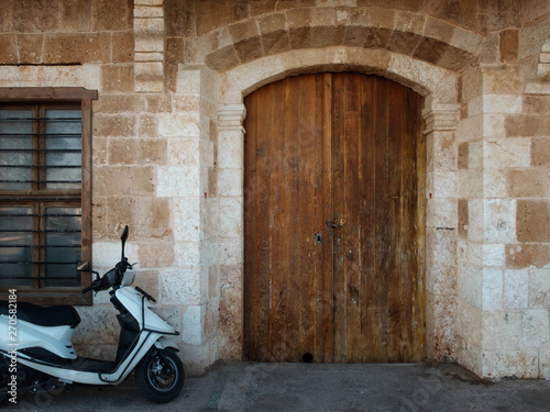 Fototapety, obrazy: Parked scooter, wooden gates and barred window of antique stone building