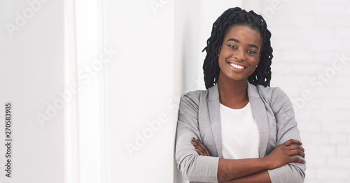 Fotografia  Businesswoman Leaning On Wall Near Window In Office
