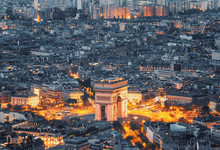 Aerial View Of The Arc De Triomphe De L'Etoile (The Triumphal Arch) In Paris At Sunset With Traffic Lights.