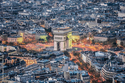 Valokuva  Aerial view of the Arc de Triomphe de l'Etoile (The Triumphal Arch) in Paris at sunset with traffic lights