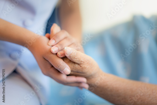 Obraz na plátně Nurse sitting on a hospital bed next to an older woman helping hands, care for t