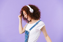 Portrait Of Pleased Redhead Curly Woman 20s Wearing Headphones Smiling While Listening To Music