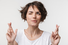 Portrait Of Cheerful Woman With Short Brown Hair In Basic T-shirt Keeping Fingers Crossed And Wishing Good Fortune