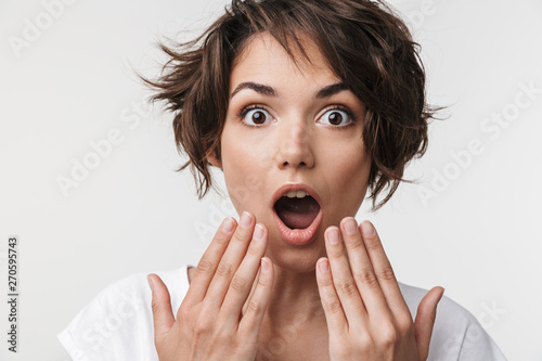 Photo  Portrait of excited woman with short brown hair in basic t-shirt covering her mo