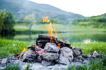 Burning Fire In Nature On The Background Of The Lake The Embers In The Fire. Burning Coal In The Bonfire.