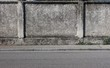 A rough concrete wall with a gray sidewalk and an asphalt road. Urban street background for copy text