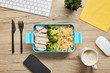 Top view of lunch box with chicken, broccoli and risotto on table with computer keyboard and smartphone