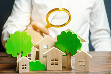 A Man Holds A Magnifying Glass Over Wooden Houses And Trees. Real Estate Valuation And Selection Of A Place For The Construction Of New Buildings. Evaluation Of Urbanism And Residential Space.