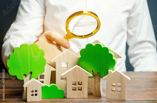 Obraz A man holds a magnifying glass over wooden houses and trees. Real estate valuation and selection of a place for the construction of new buildings. Evaluation of urbanism and residential space. - fototapety do salonu
