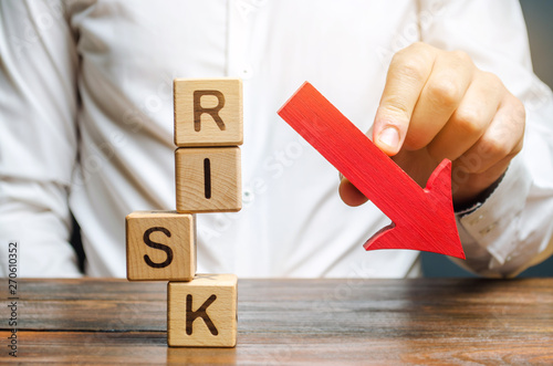 Fotografie, Obraz  Wooden blocks with the word Risk and a down arrow