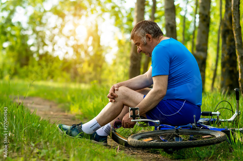 Fotografie, Obraz  an elderly man hurt his leg while riding a Bicycle