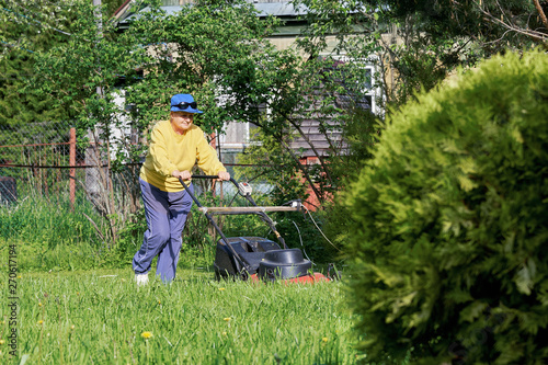 Happy elderly woman mows the lawn with an electric lawn mower on allotment in a warm sunny day Wallpaper Mural