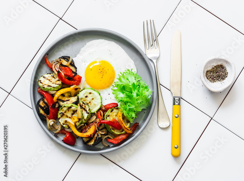 Photo  Delicious breakfast or snack - grilled vegetables and fried egg on a light backg