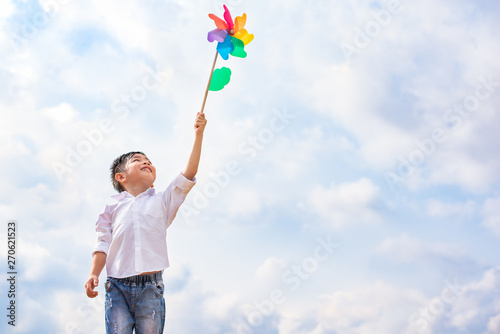Boy holding colorful pinwheel in windy at outdoors Tablou Canvas