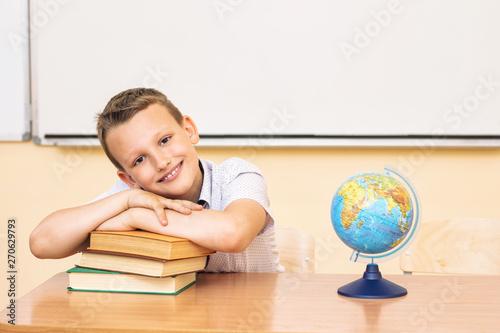 Fototapeta Boy child schoolboy happy, funny and cute with smile - portrait in classroom sitting at Desk obraz na płótnie