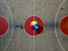 Person With Colored Umbrella On A  Basketball Court