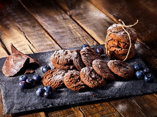 Serving food on slate onto wooden table. Oatmeal cookies biscuit with blueberry on picnic dark tiles countrylike. Chocolate chip cookies tied with string. Cooking desserts at home.