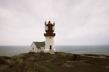 Lindesnes Fyr, Norway, A Red And White Lighthouse With The Misty Sea In The Background.