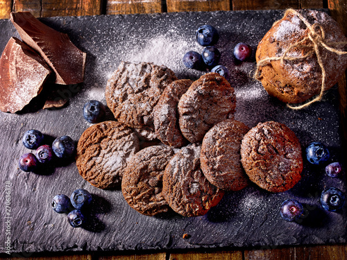 Serving food on slate onto wooden table. Oatmeal cookies biscuit with blueberry on picnic dark tiles countrylike. Chocolate chip cookies tied with string. Bakery products. Perfect product.