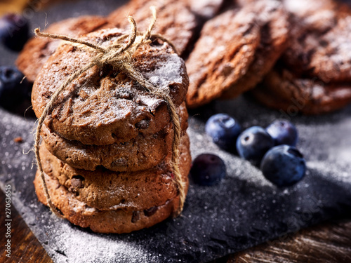 Serving food on slate onto wooden table. Oatmeal cookies biscuit with blueberry on picnic dark tiles countrylike. Chocolate chip cookies tied with string. Best range of confectionery products.
