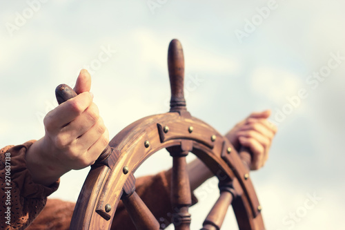 Canvas Prints Ship Steering hand wheel ship on sky background, hand hold hand wheel