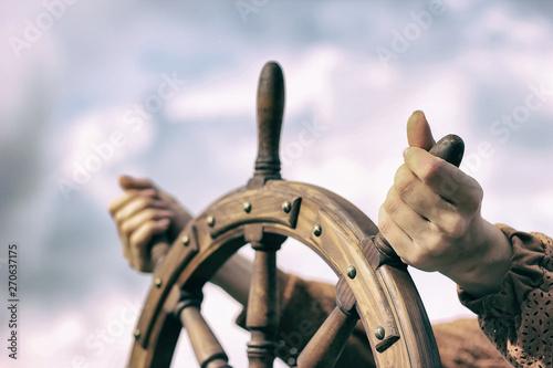 Cuadros en Lienzo Steering hand wheel ship on sky background, hand hold hand wheel