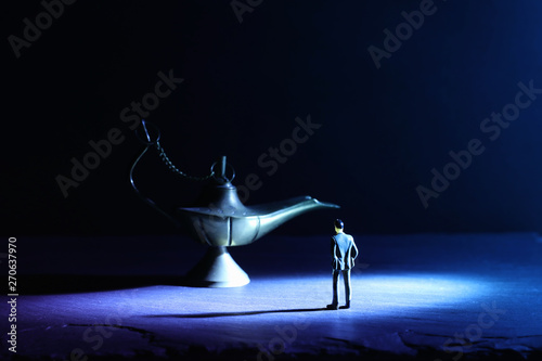 Obraz na plátně  Concept picture of a businessman looking at Aladdin lamp asking for a wish