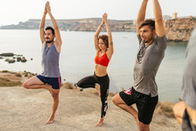 Group Of People Doing Yoga At The Cliff